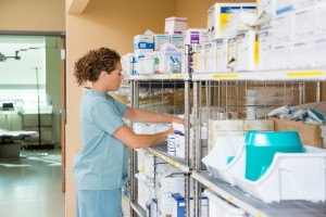 Side view of mid adult female nurse working in storage room of cancer hospital