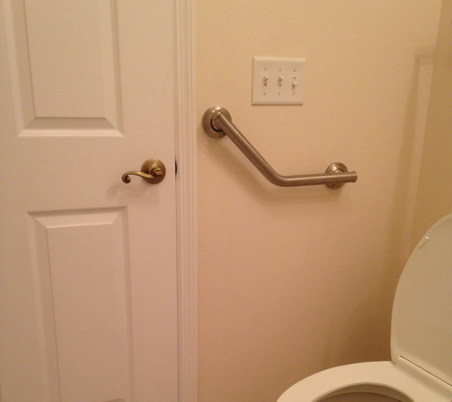 wall mounted grab bar next to toilet